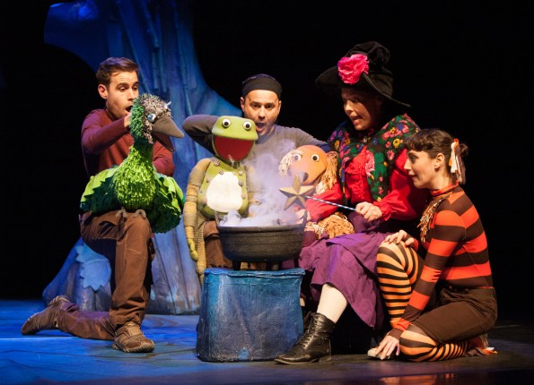 the cast around a cauldron on stage