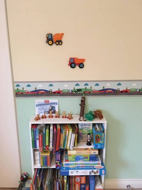 book case with books and trucks on a wall