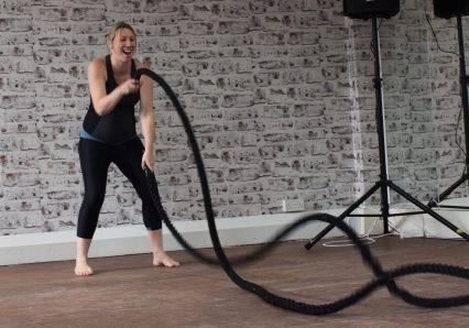 pregnant lady in activewear doing battle rope