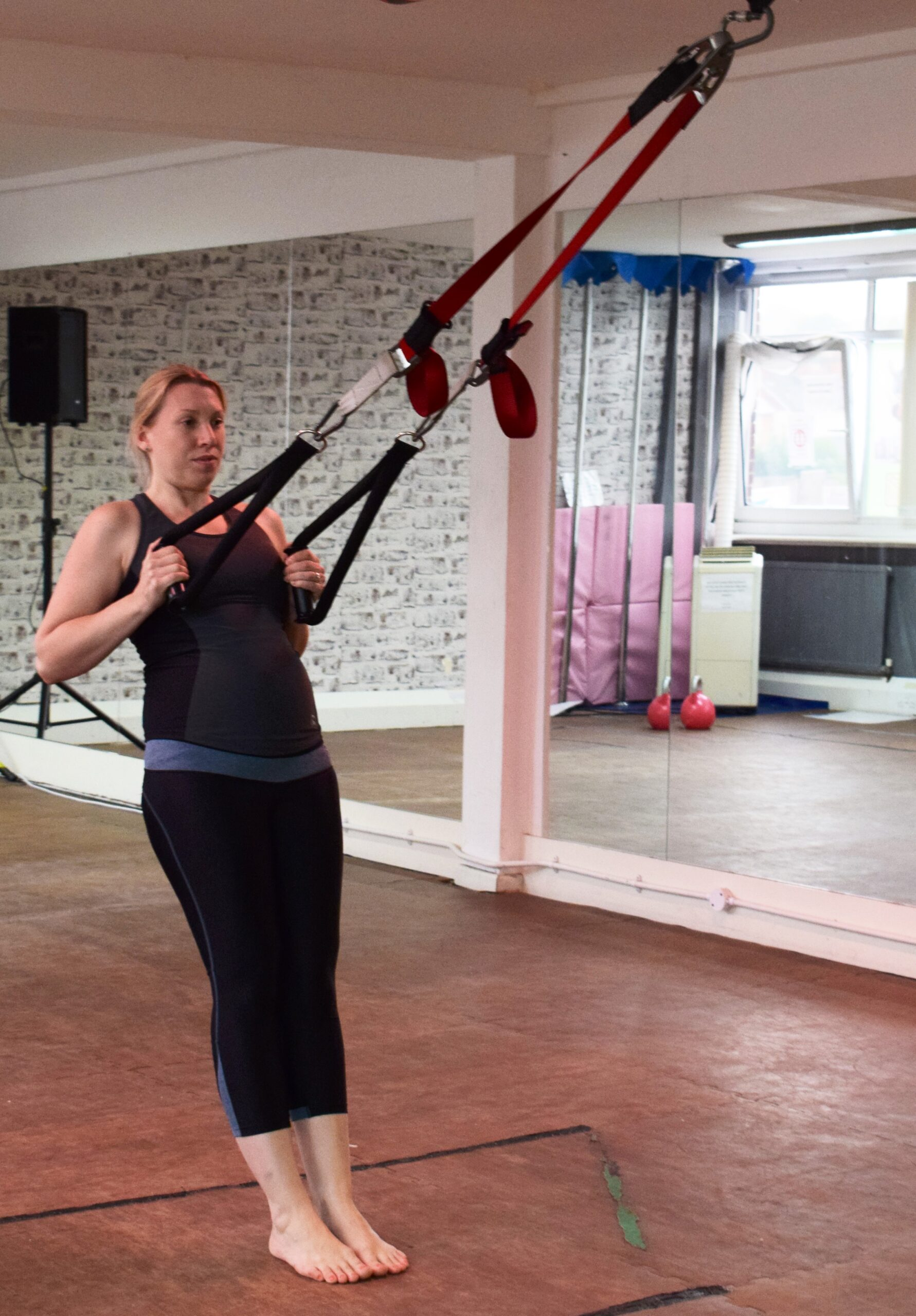 pregnant lady in activewear using TRX