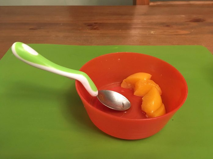 bowl of peaches and spoon