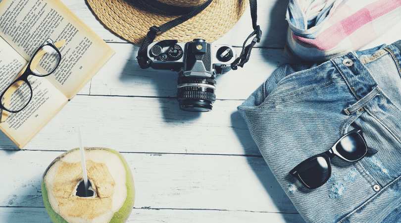 flat lay of a camera, jeans, sunglasses, fruit, galsses and a book for holiday travel