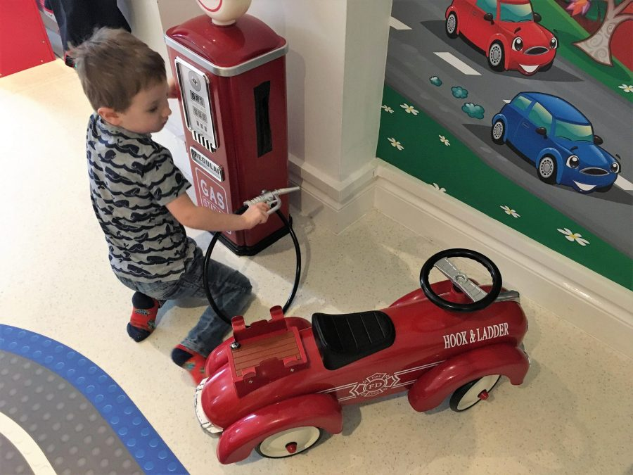 Jake pretending to fill up a toy car with petrol