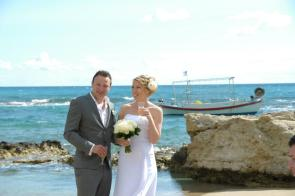 me and Rob holding a glass of champagne and smiling on the beach on our wedding day