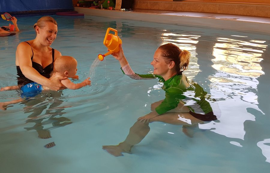 me and william in the pool with the teacher pouring water from a watering can