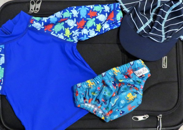 suitcase with a reusable swim nappy, a hat and a swim top on top of it