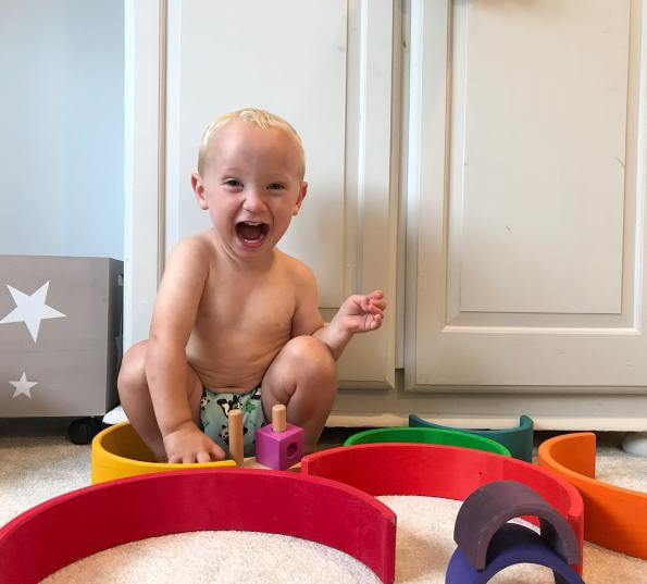 toddler sat in a cloth nappy with his mouth open like he is shouting