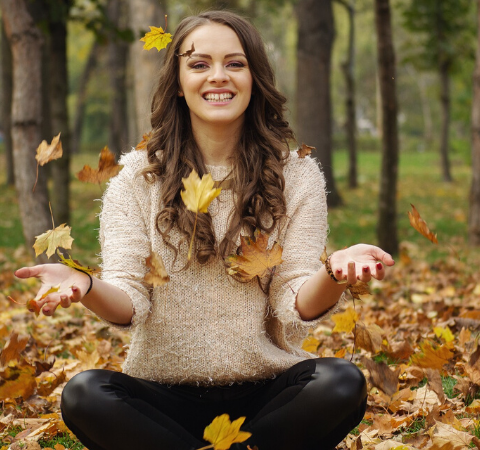 lady sat in woods throwing leaves up looking stylish