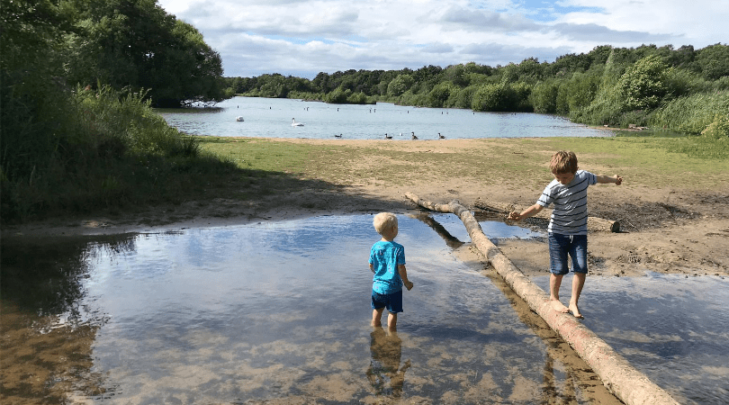 2 boys in water, one balancing on a log and the other paddling