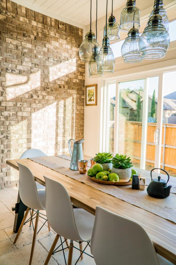 a clean and elegant kitchen diner with oak table and hanging lights