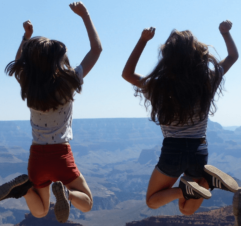 2 girls jumping in the air excitably at being at The Grand Canyon