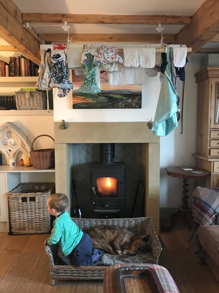 a pulley maid with cloth nappies hanging above a log burner in a cottage