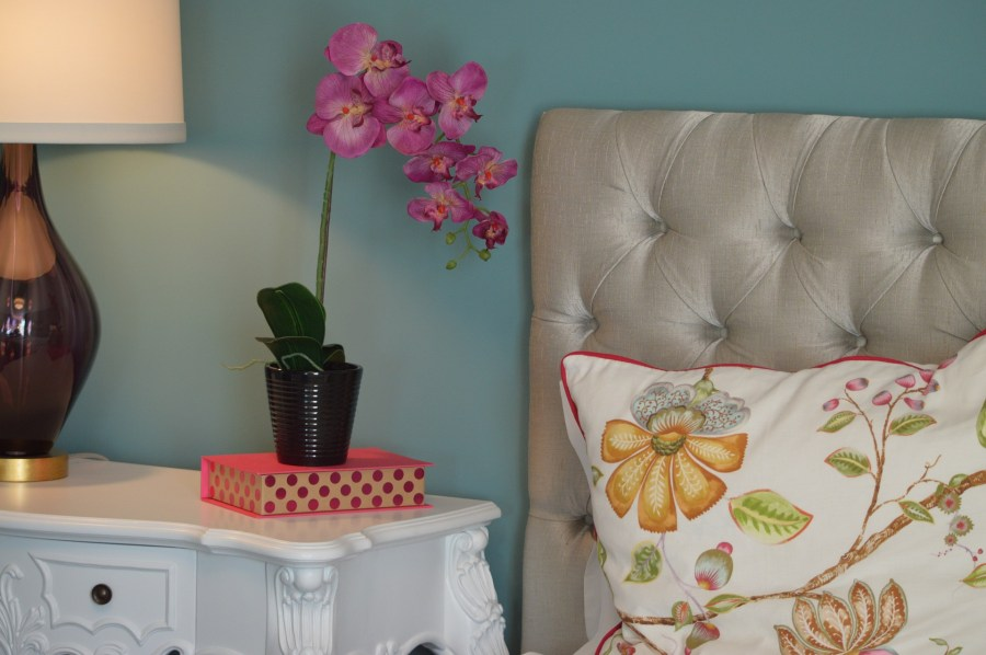 a blueish green wall with an orchid and a bed