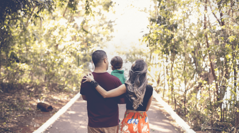 a family of three walking fown a path with trees around them