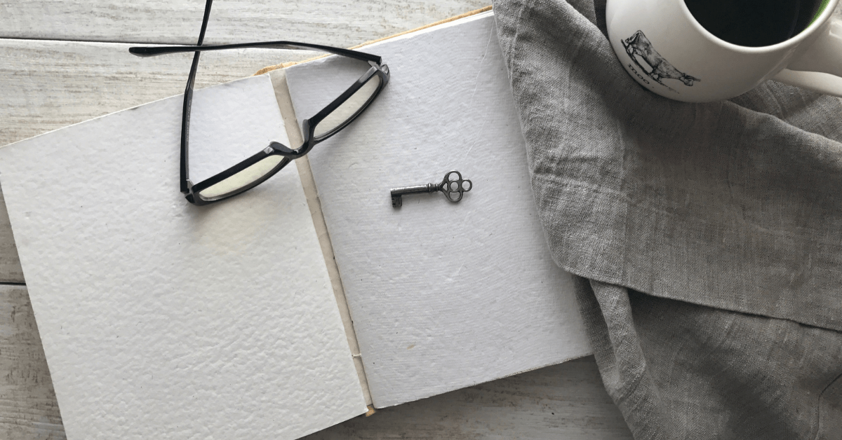 glasses laid on a book with blank pages and a tiny key