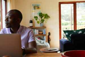 thoughtful black man with laptop at home