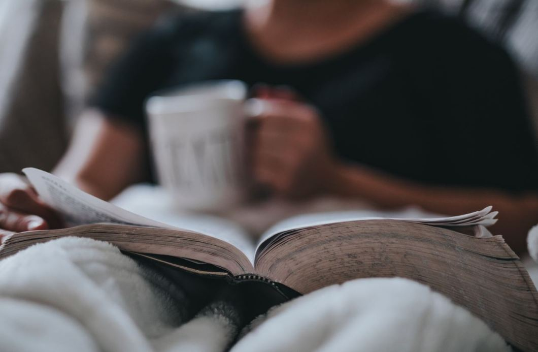 Man reading book with coffee mug while relaxing in bed