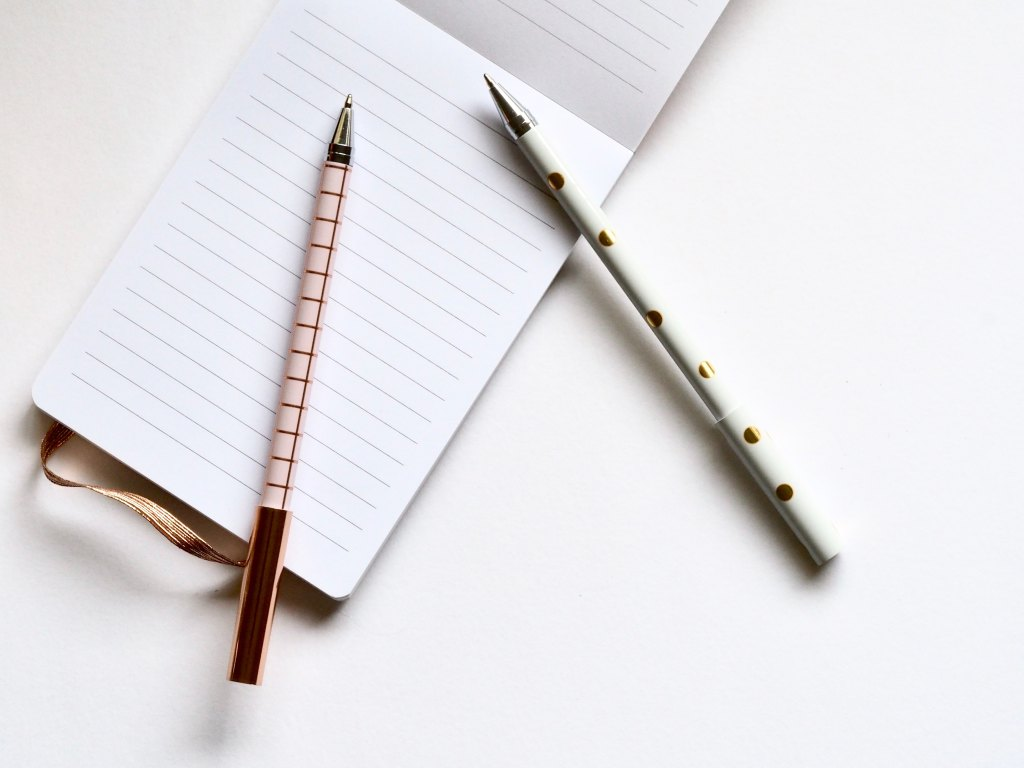 two pens and notepad on desk