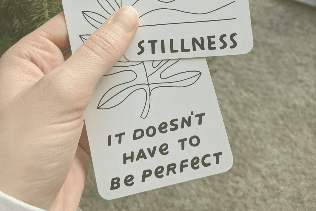 "A hand holds two oracle cards. One reads ""It Doesn't Have to Be Perfect"" and the other shows the word ""Stillness."""