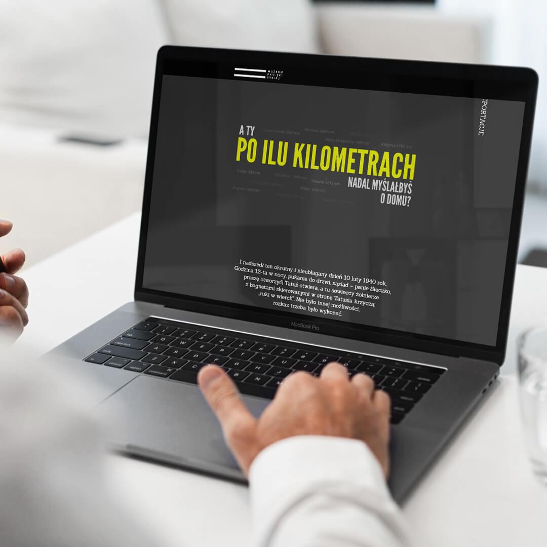 Grafika przedstawia zdjęcie komputera typu laptop. Na ekranie widzimy stronę internetową poilukilometrach.pl
