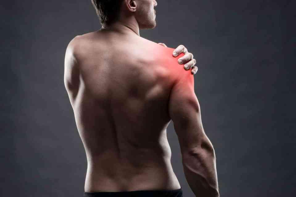 Fit man holding shoulder, shoulder pain during exercise