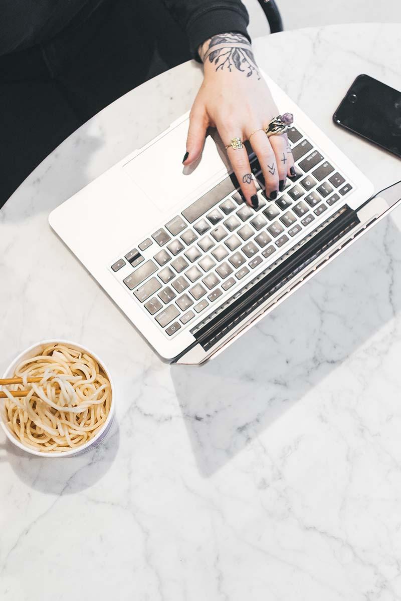a imagem mostra uma mulher em frente a um notebook trabalhando enquanto come macarrão oriental.