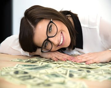 Happy woman sitting at the table with money