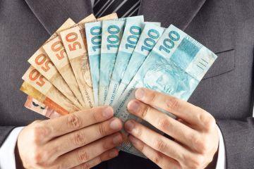 Uma pessoa segurando dinheiro, representando o empréstimo consignado