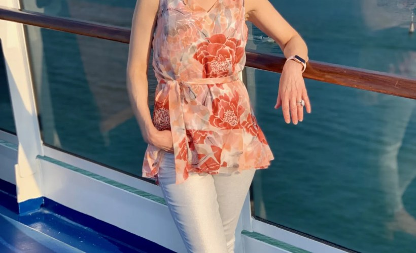 woman standing at the rail of a cruise ship dressed in floral top and silver jeans