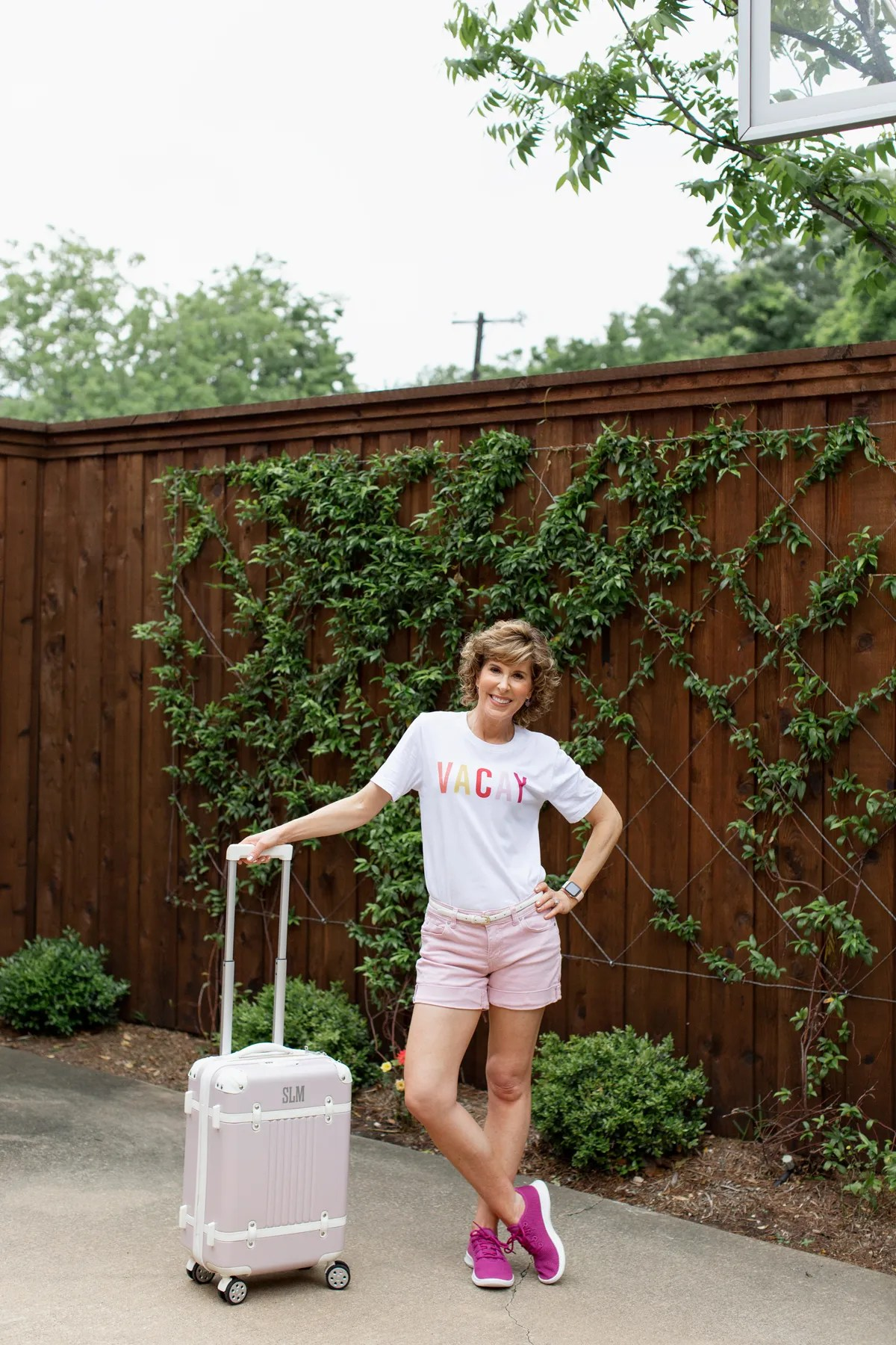 woman wearing vacay tee posing with blush carry-on suitcase