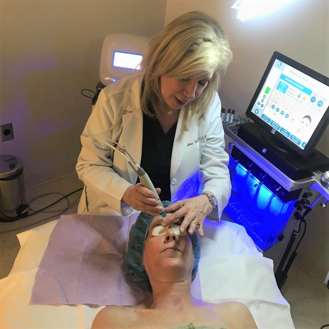 aesthetician doing facial on woman lying on bed