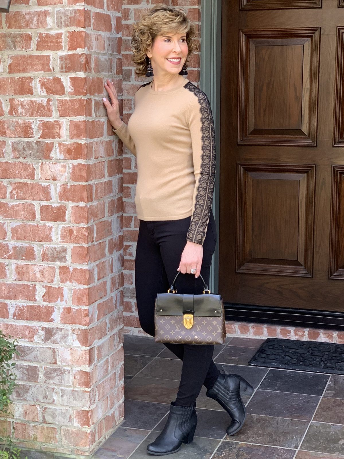woman in tan with black accent sweater leaning against doorway
