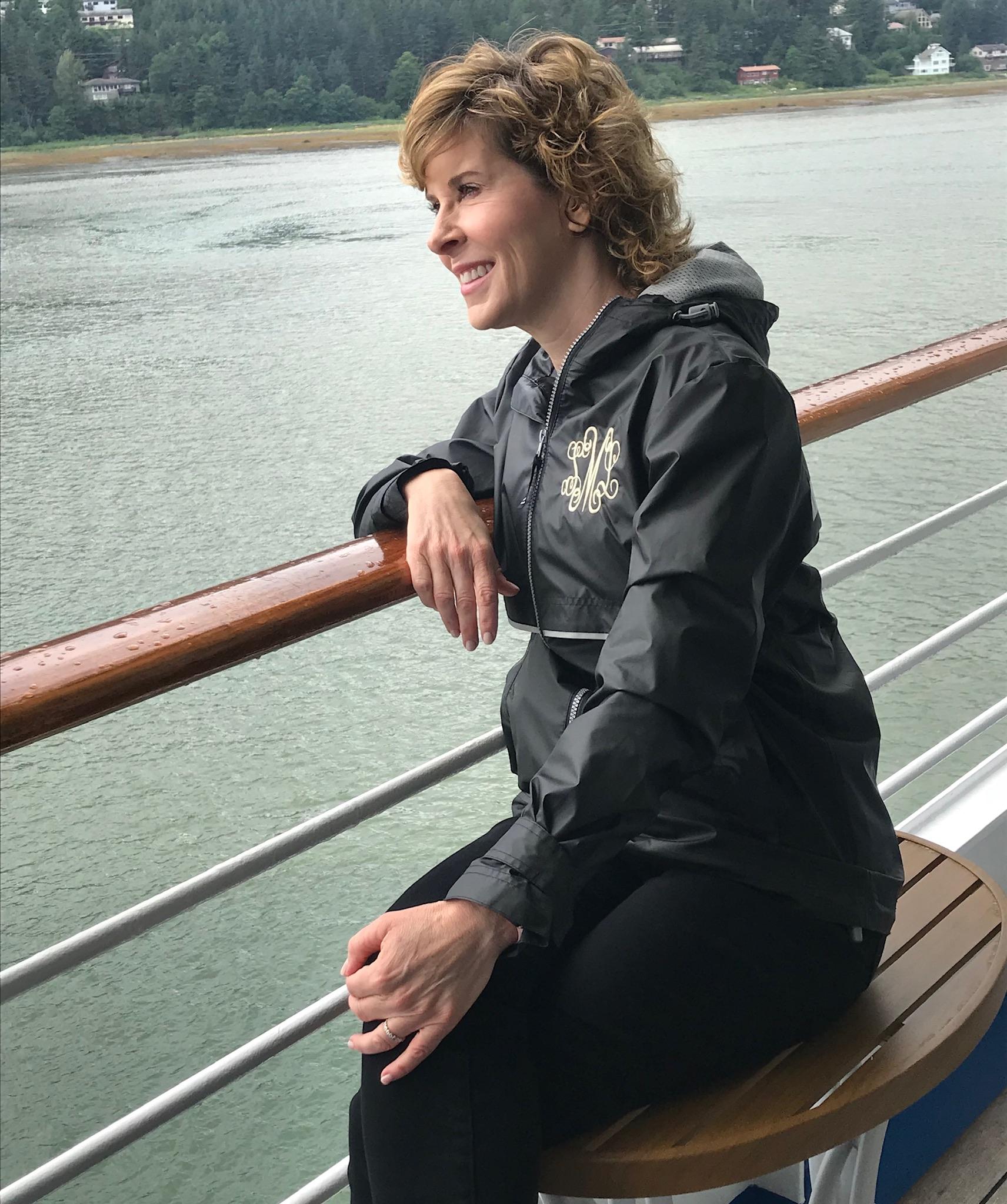 woman in black monogram rain jacket looking over ship railing