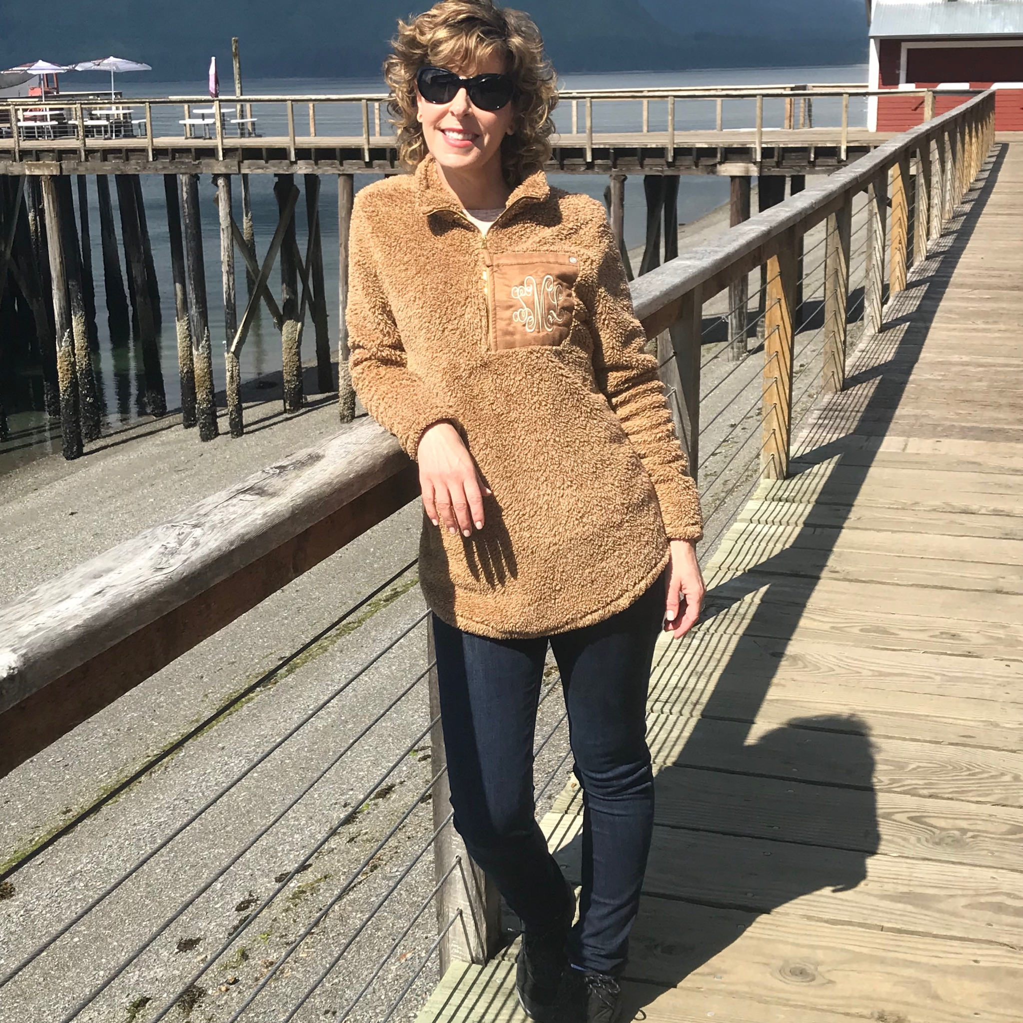 woman in tan fuzzy tunic leaning against railing