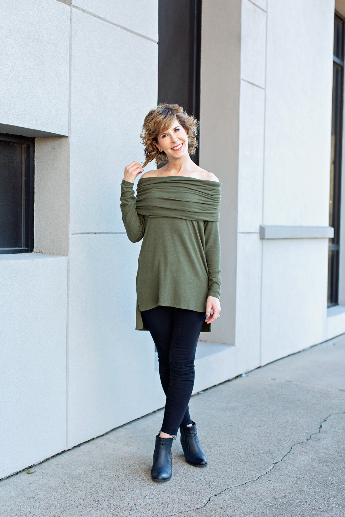 woman in green off shoulder sweater touching her hair