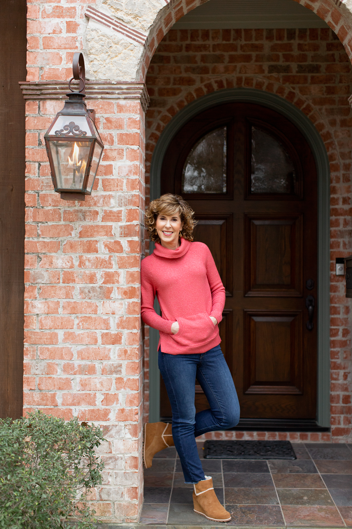 woman in coral sweater standing in brick arch doorway