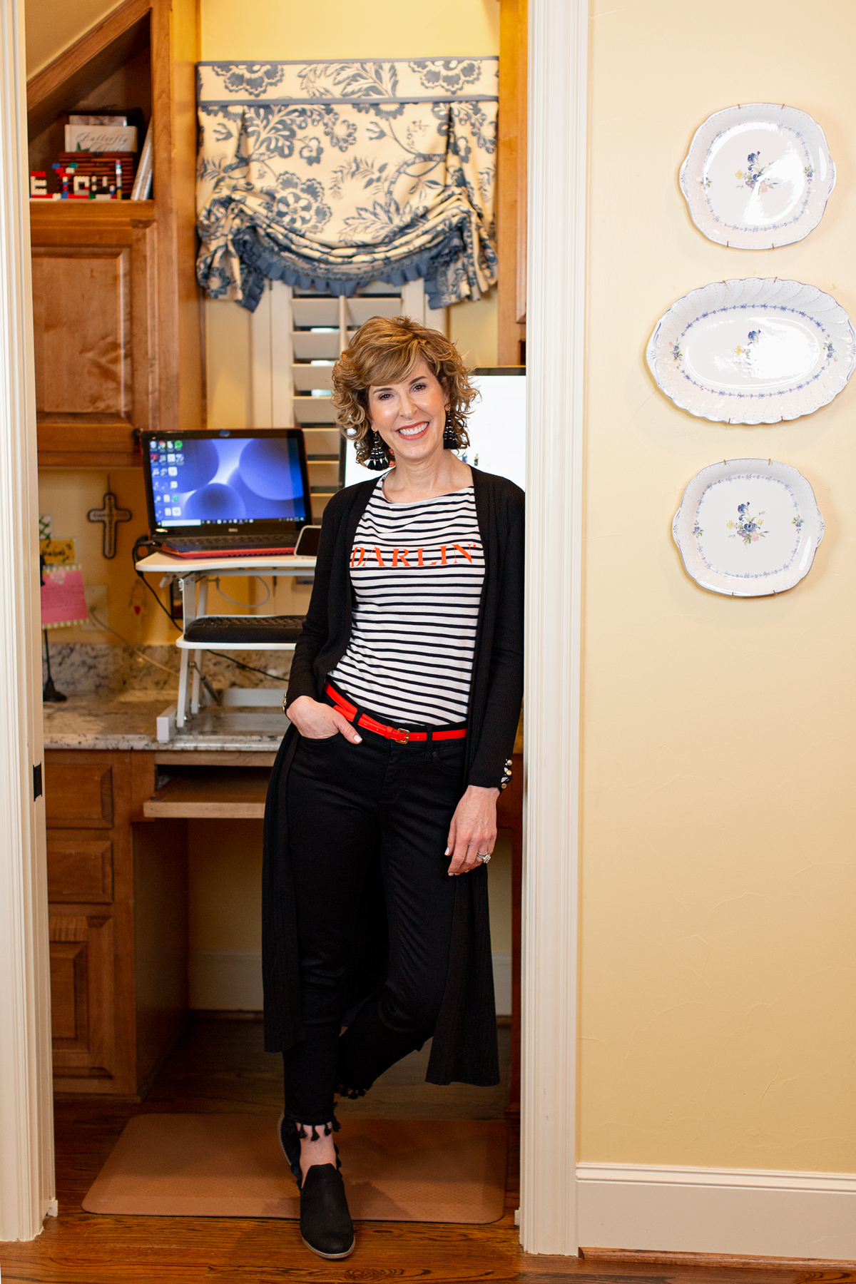 woman in striped shirt leaning against home office doorway