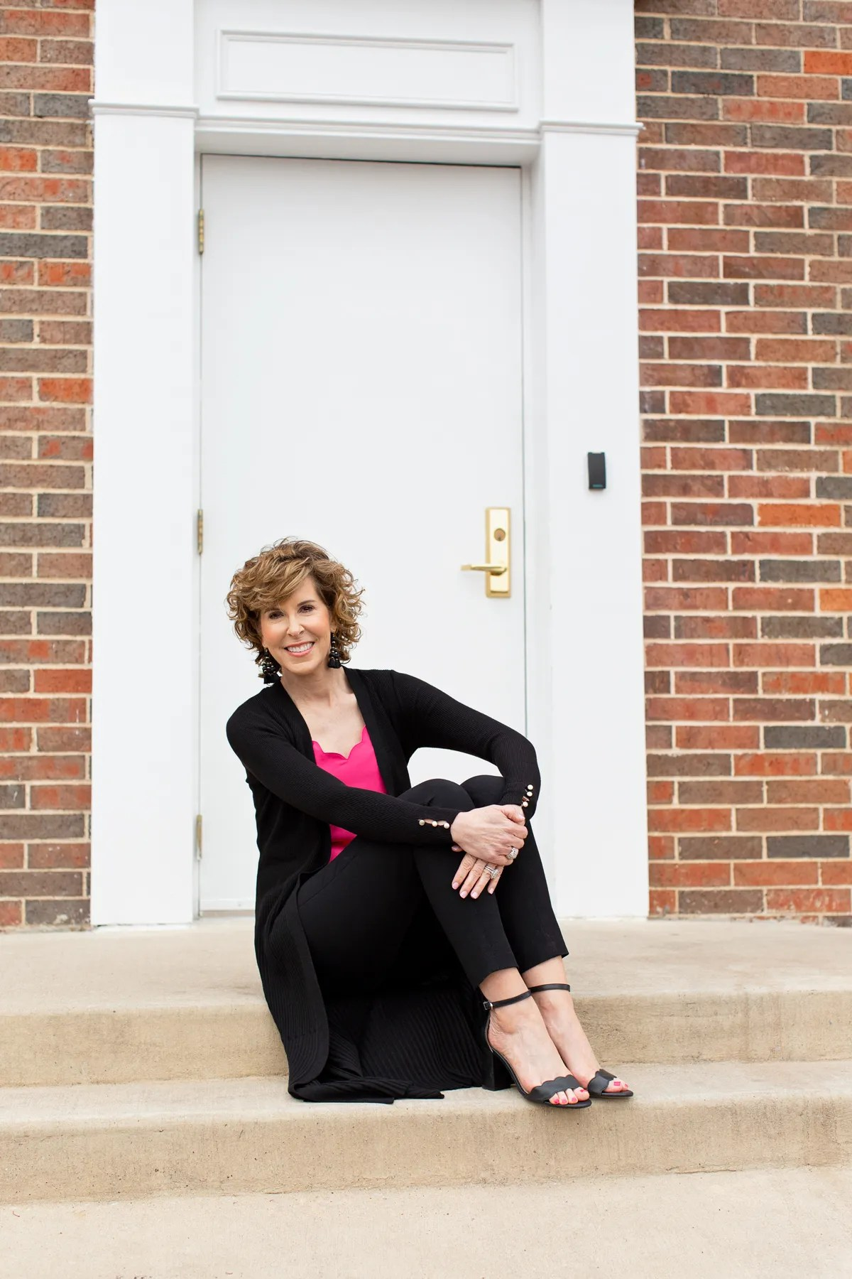 woman sitting in front of doorway in pink top with black sweater