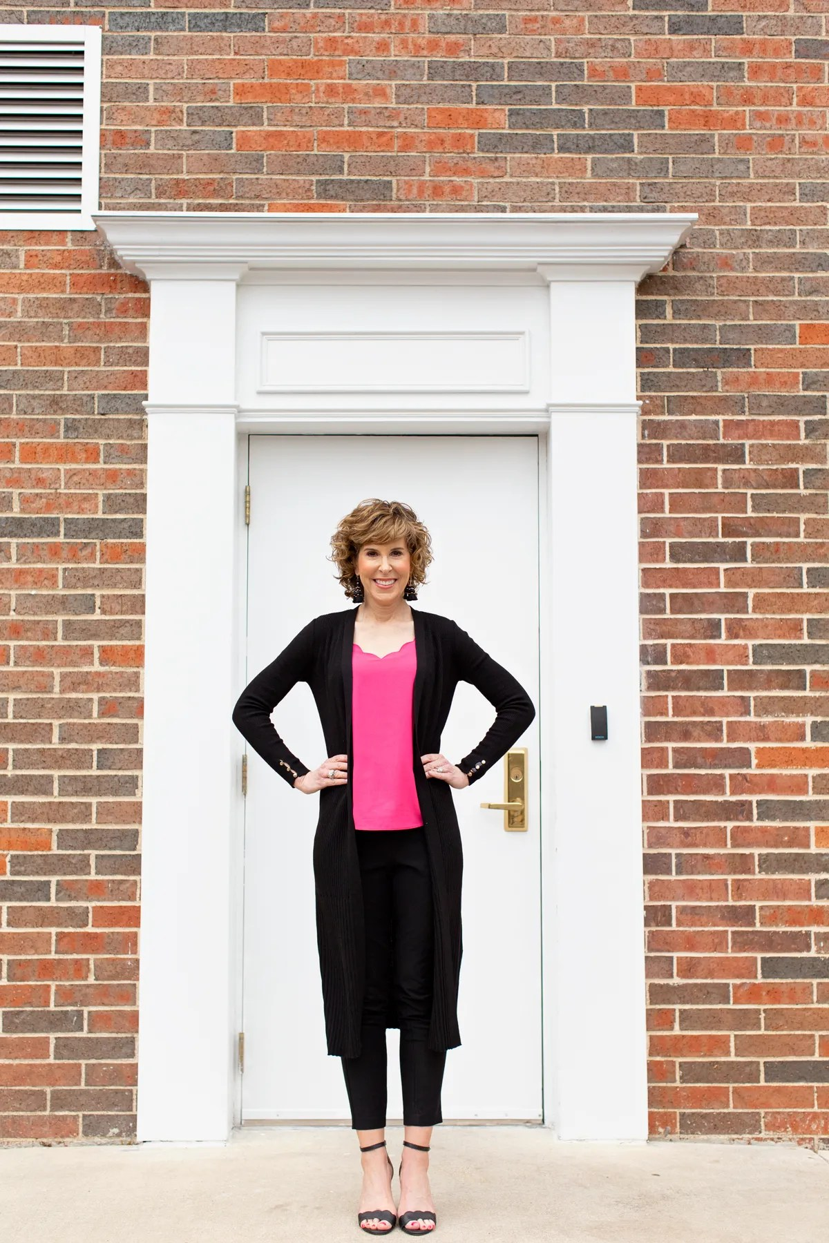 woman with hands on hips standing on porch