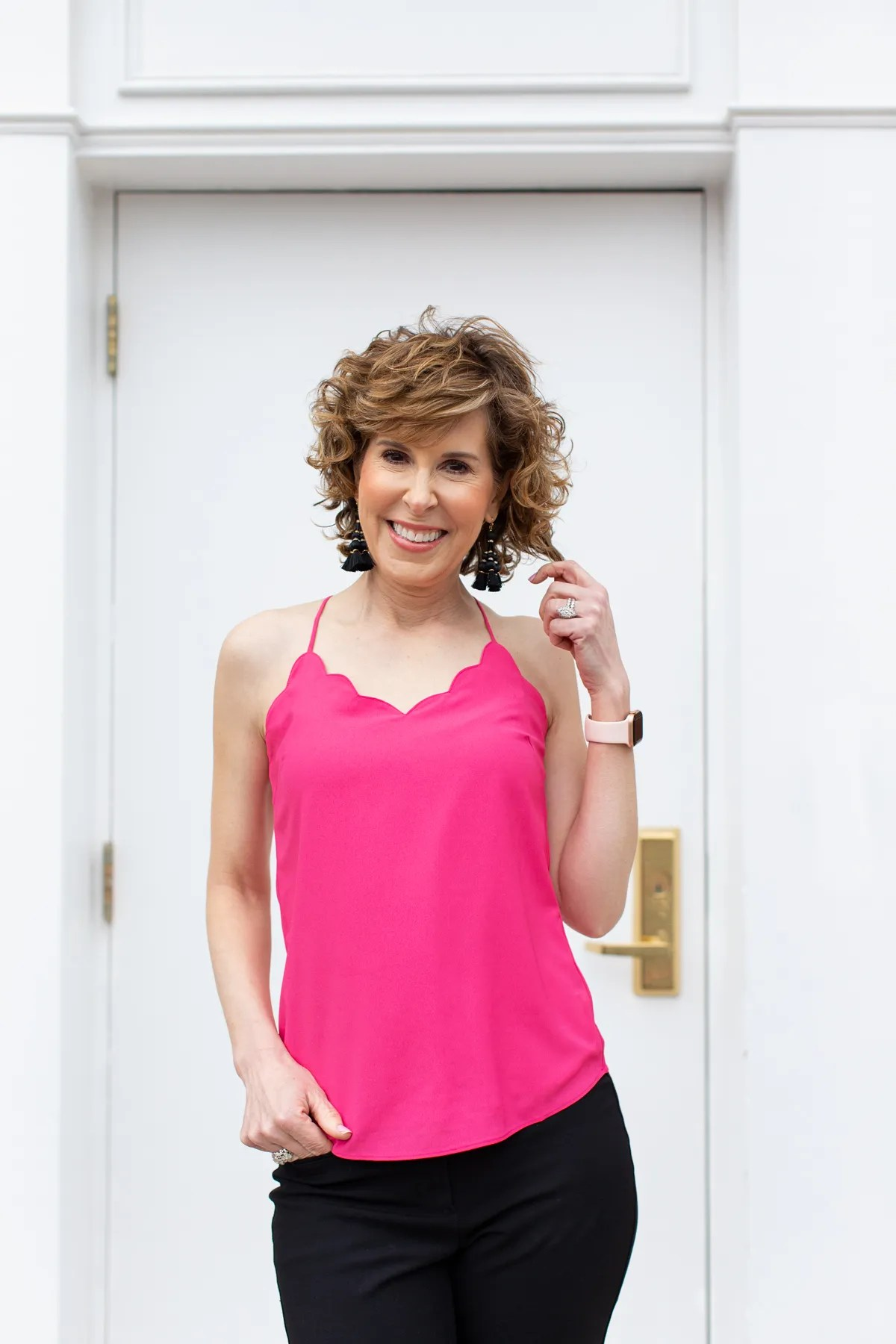 woman standing in front of doorway wearing pink top