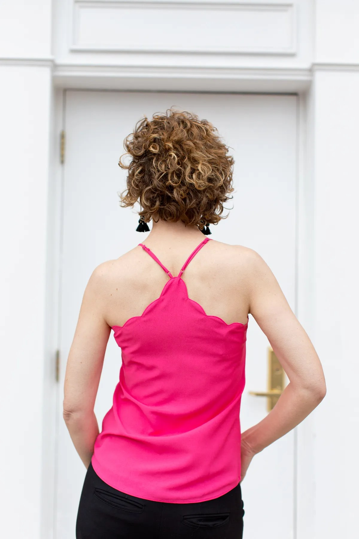 woman standing in front of doorway wearing pink top with back to the camera