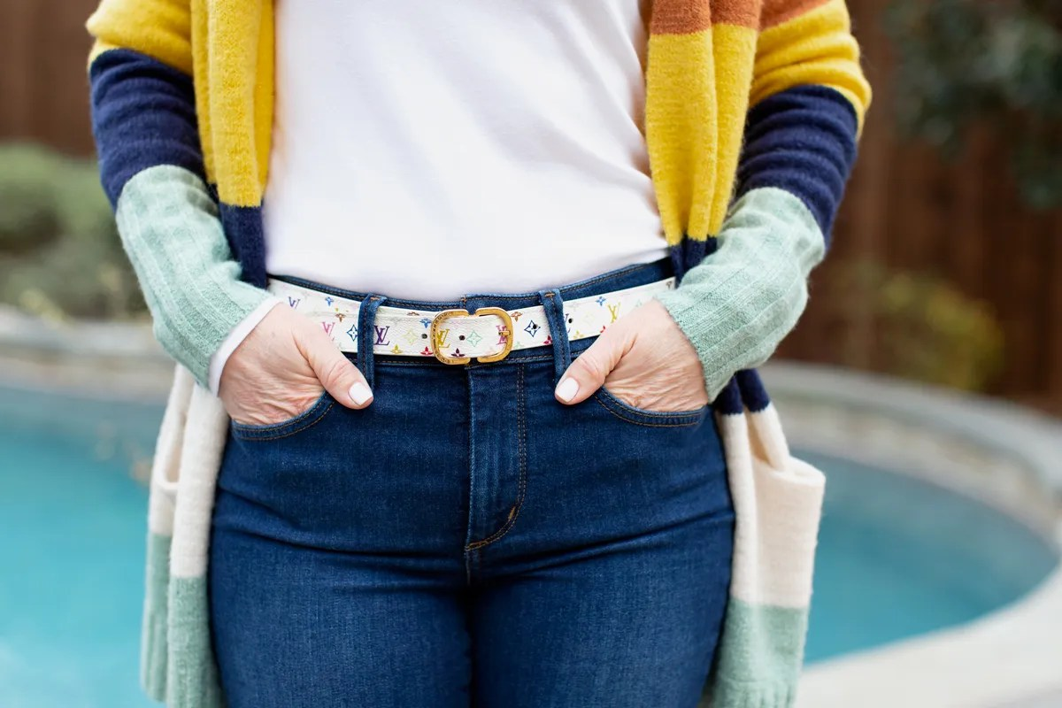 womans wearing designer belt with hands in jean pockets
