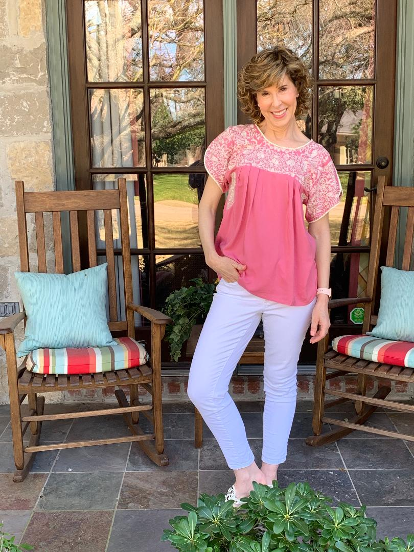 woman wearing pink shirt and white jeans standing on front porch