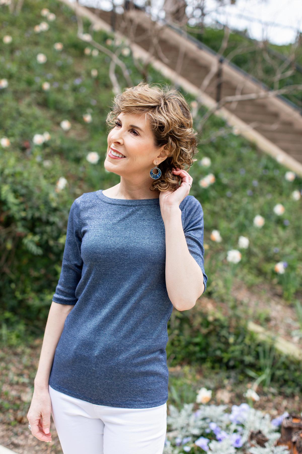 woman in blue tee tucking hair behind her ear