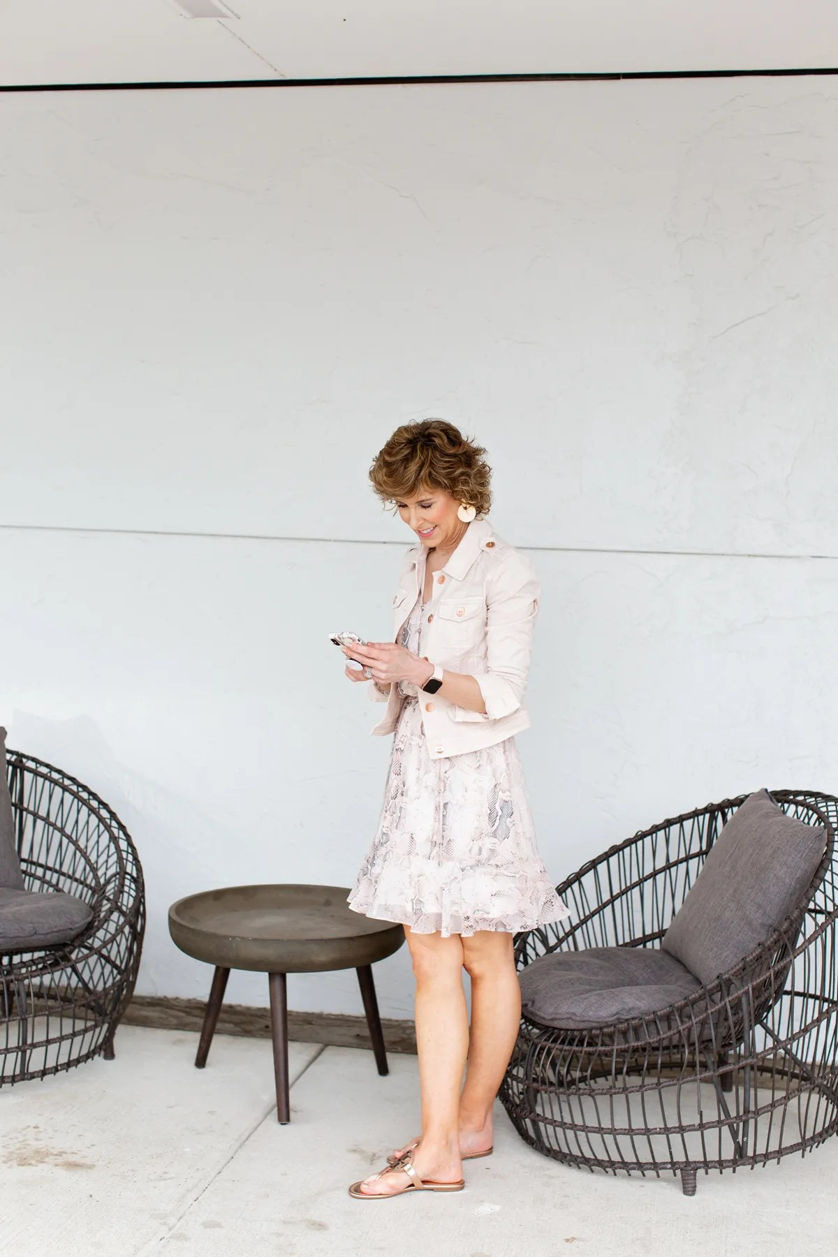 woman wearing blush jacket holding her phone and looking at phone