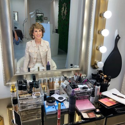 woman sitting at a makeup table