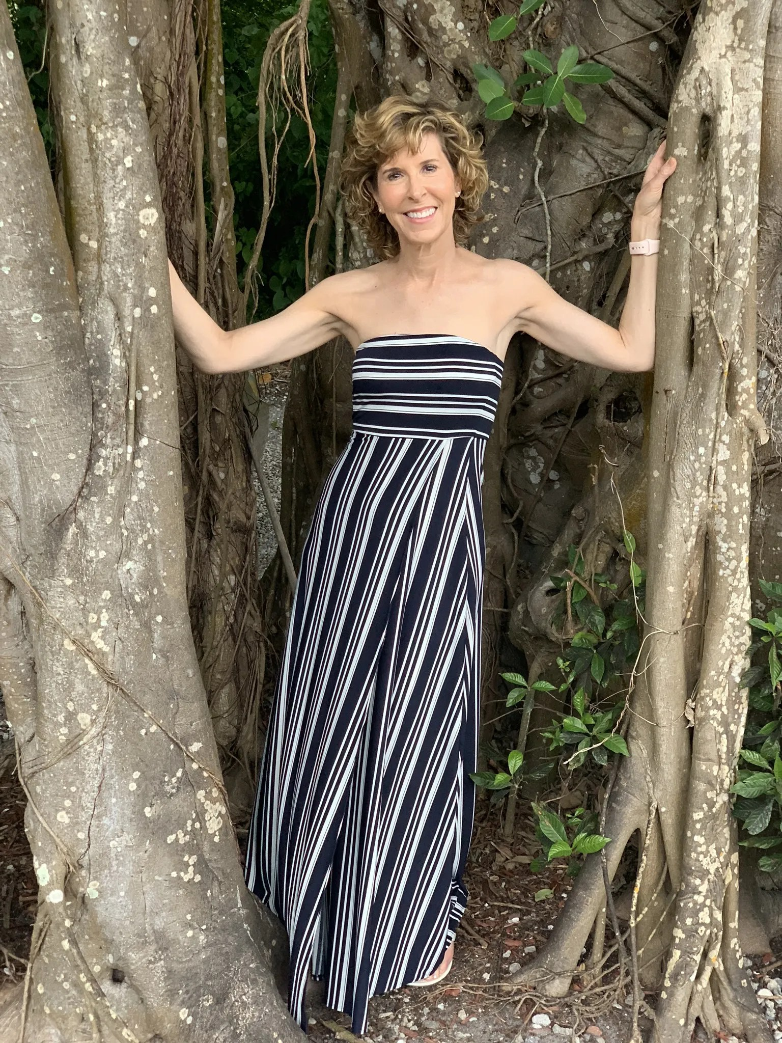 woman wearing blue and white maxi dress standing inside a tree trunk