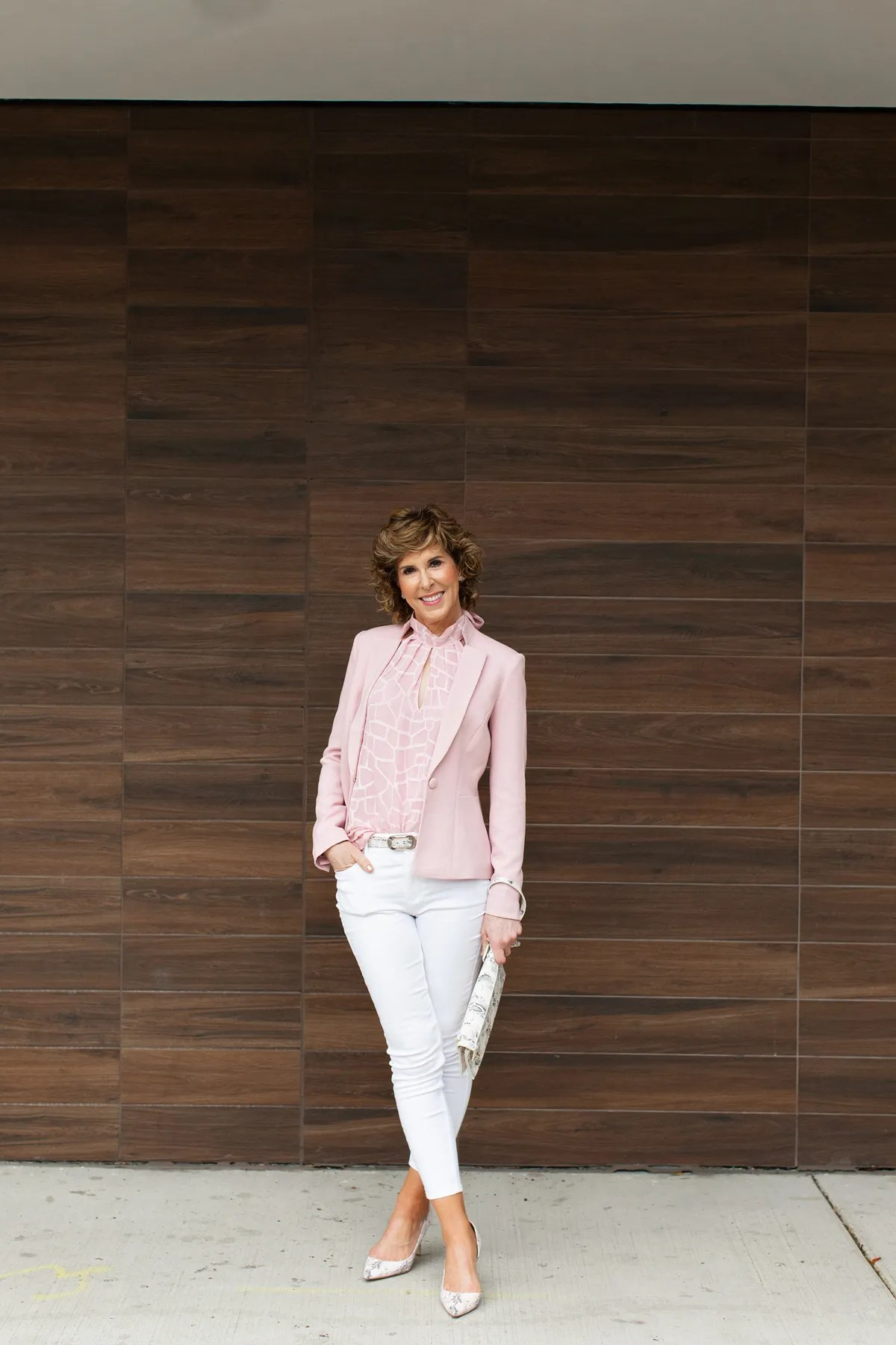 woman over fifty wearing pink top and blazer standing in front of a brown wall and looking at the camera