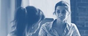 Two women engaged in conversation - blue tone.