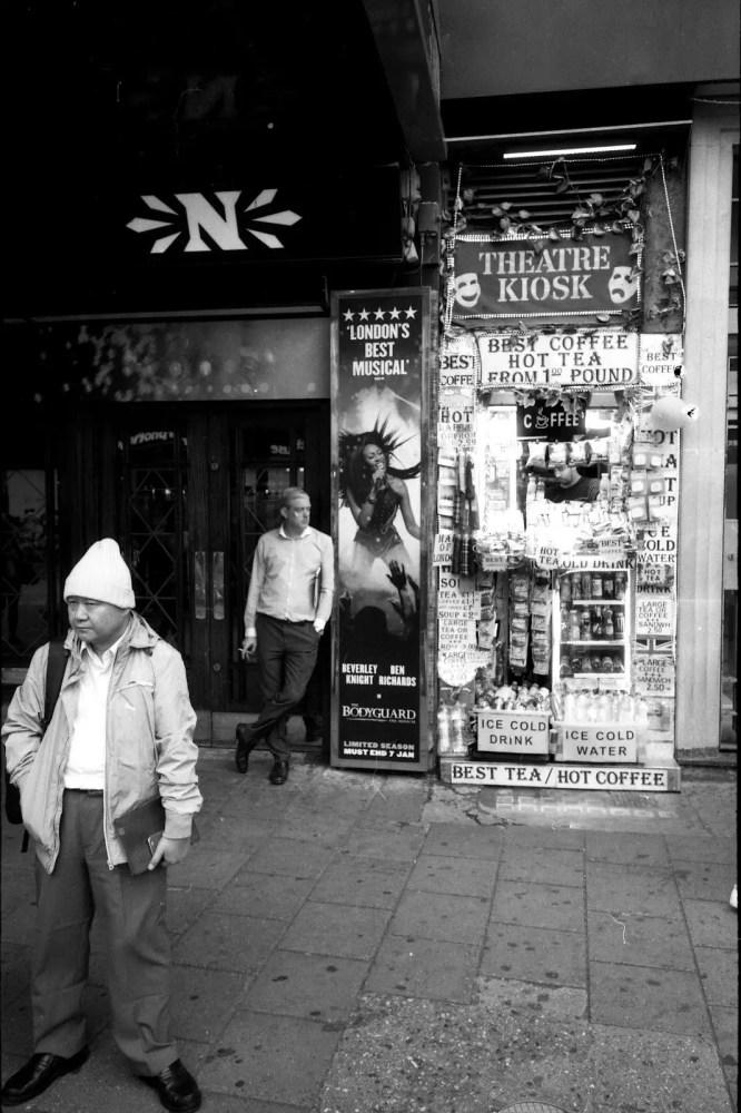 Two men waiting outside a theatre near Tottenham Court Road, London